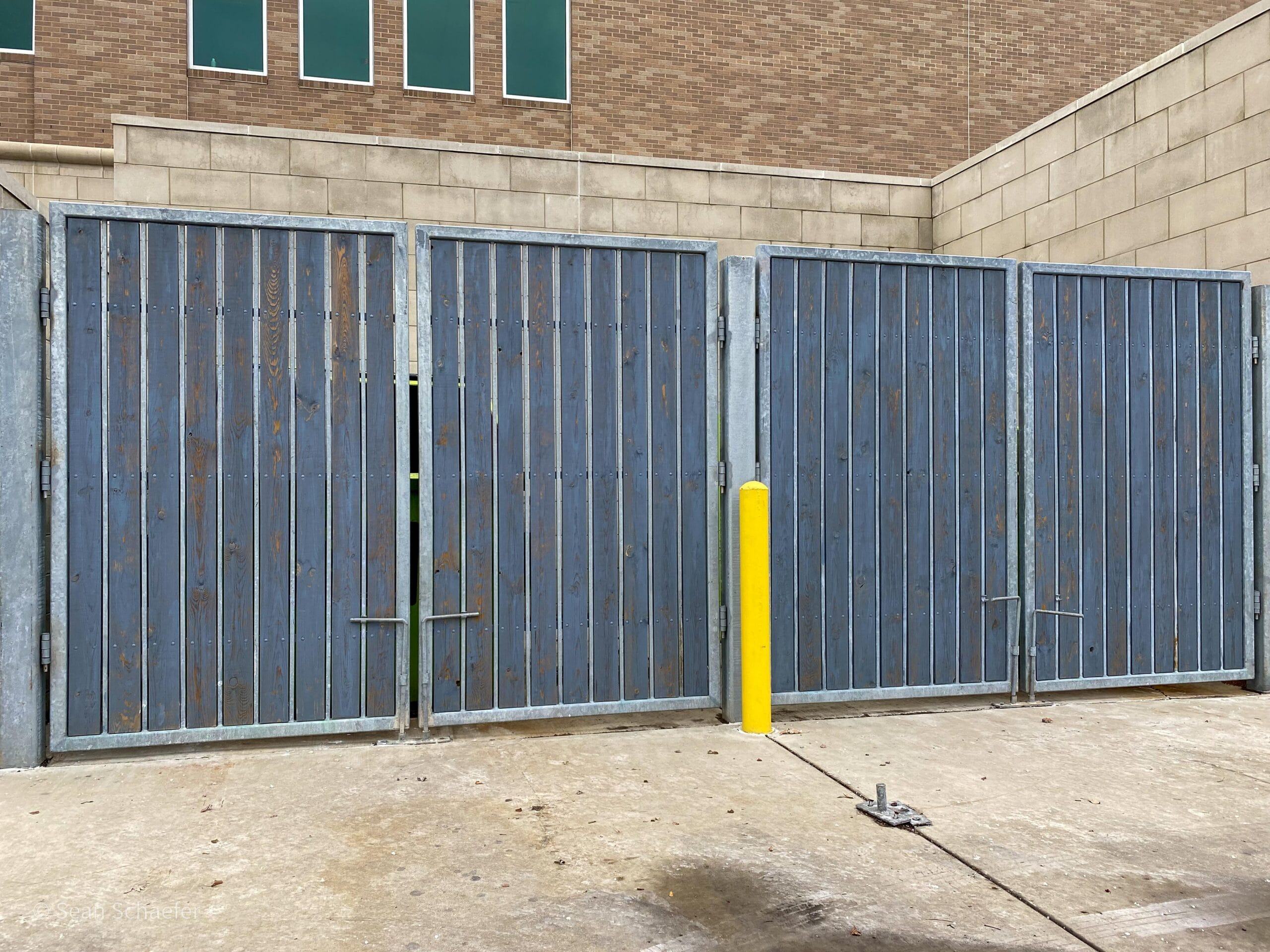 Hero image of commercial wood and galvanized steel dumpster gates at Michigan First Credit Union