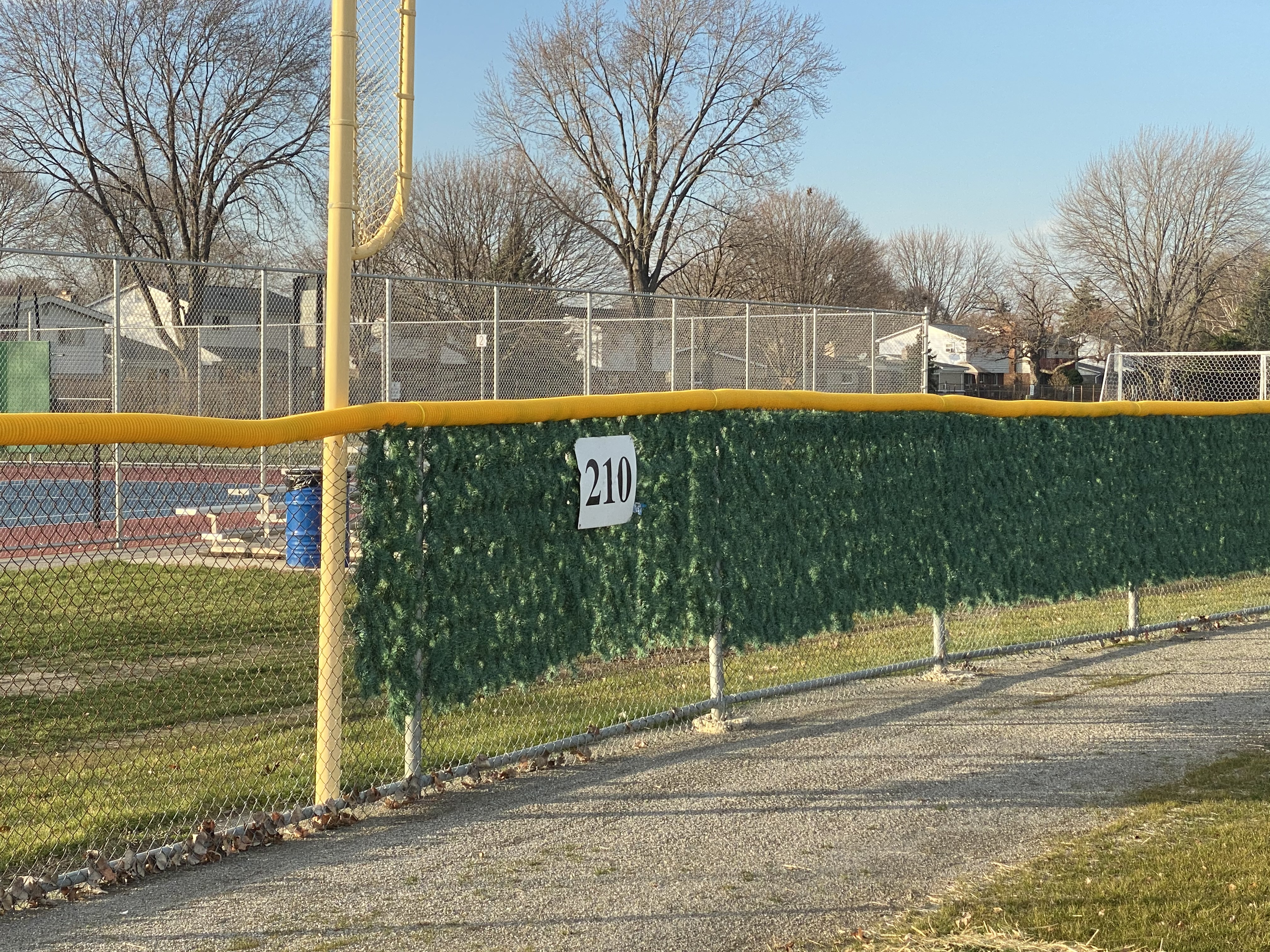 Image of commercial chain link baseball diamond fencing, PVC top cap, and Christmas tree slats at Cousino High School